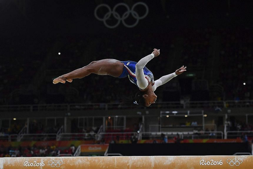 US gymnast Simone Biles executing a back flip on the beam during the all-around final. She is in the beam, vault and floor apparatus finals as well.