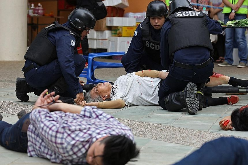 """Singapore Civil Defence Force officers attending to """"victims"""" during a mock terror attack staged in Toa Payoh Lorong 1 last Saturday. The issues up for debate in Parliament on Monday include Singapore's fight against terrorism, with Dr Fatimah asking"""