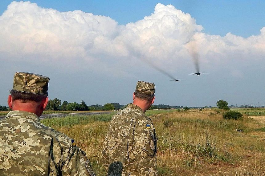 Ukrainian soldiers watching Sukhoi Su-24 front-line bombers during military aviation drills in the Rivne region in Ukraine on Wednesday.