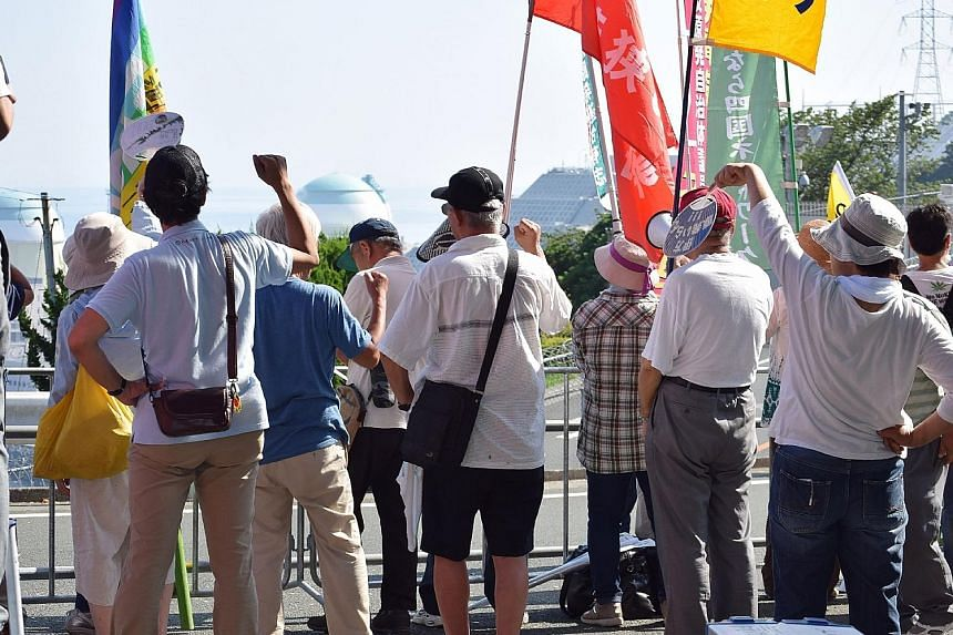 Residents and others opposing the restart of the Ikata nuclear reactor gathering near the plant in Ehime prefecture, about 700km south-west of Tokyo, yesterday. Opposition to nuclear power has seen communities across the country file lawsuits to prev