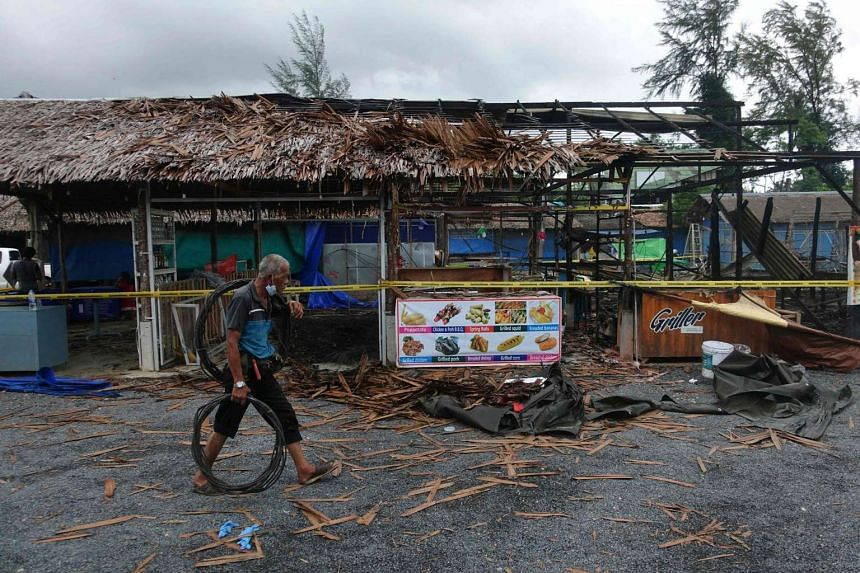 A man walks past the site of a small bomb blast and arson attack on Bang Niang market, Takua Pa, near Khao Lak in Phang Nga province of Thailand on Aug 12.