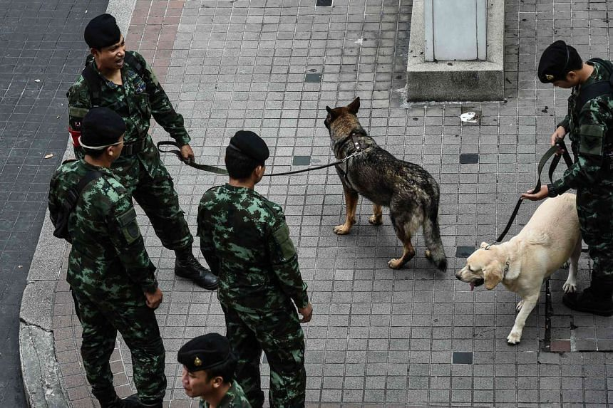 Thai soldiers and sniffer dogs stand near Erawan Shrine, a popular tourist destination that was the site of a bomb attack almost one year ago, in Bangkok on Aug 12.