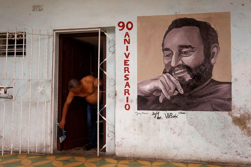 A man cleans the doorstep of his home with an image depicting Cuba's former President Fidel Castro and writing that reads 90 Anniversary in Havana, Cuba.