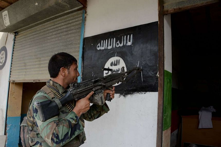 An Afghan soldier points his gun at an ISIS banner during a patrol on July 26, 2016.