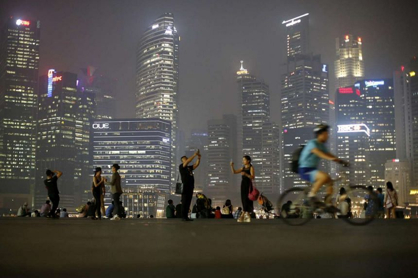 People take photos with the skyline of the central business district in Singapore on Sept 10, 2015.