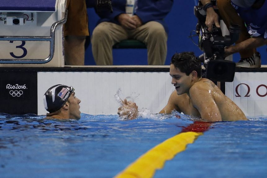 USA's Michael Phelps congratulates Joseph Schooling after he wins the gold for 100m men's butterfly final.
