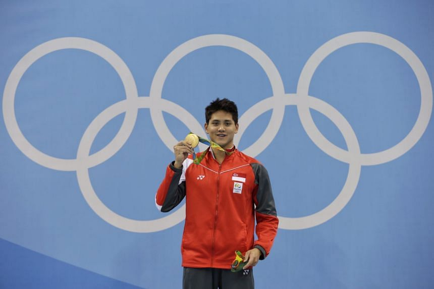 Joseph Schooling holding his gold medal at the men's 100m butterfly victory ceremony on Aug 12.
