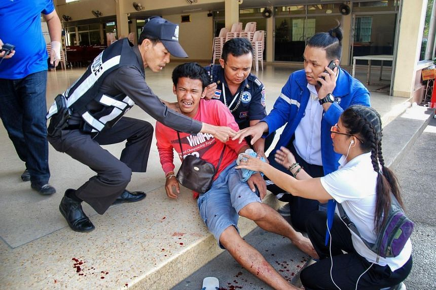 A man is treated for injuries at the scene of a bomb explosion in the upscale resort town of Hua Hin on Aug 12.