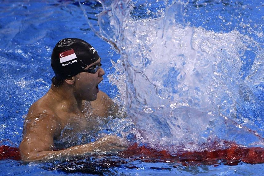 Joseph Schooling slaps the water in delight after winning the 100m butterfly final.