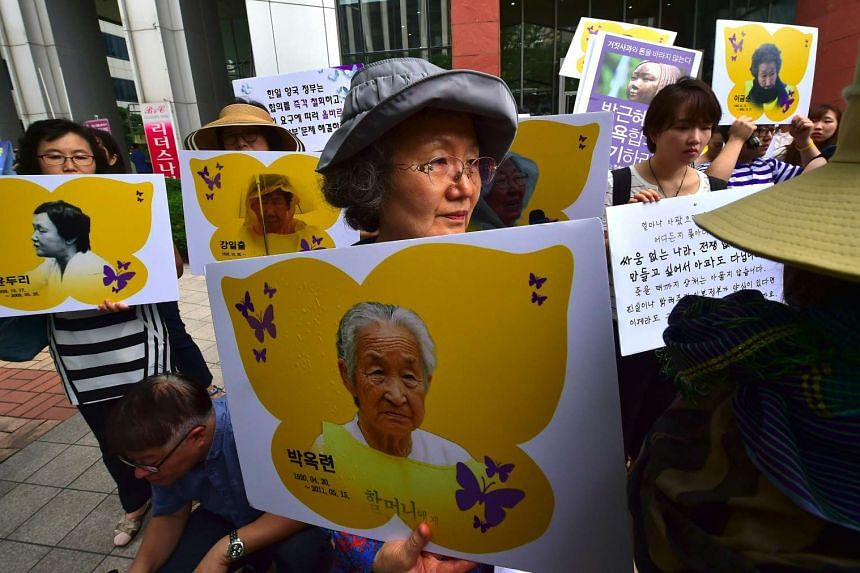 South Korean protesters holding placards showing former comfort women during a rally in Seoul on July 28, 2016.