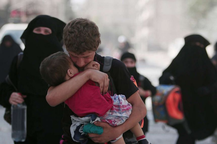 A man carries a child after they were evacuated by Syria Democratic Forces fighters from an ISIS-controlled neighbourhood in Manbij on Aug 12, 2016.