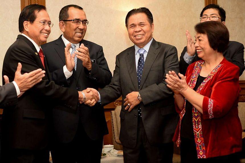 Presidential adviser on the peace process Jesus Dureza (left) shaking hands with MILF chairman Murad Ibrahim (centre) on Aug 13, 2016.