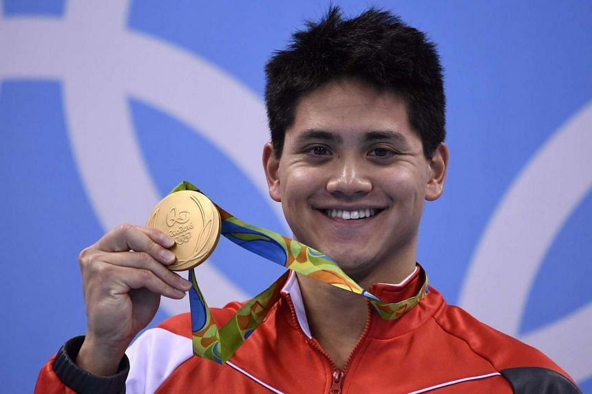 Joseph Schooling poses with his gold medal on the podium of the men's 100m butterfly final.