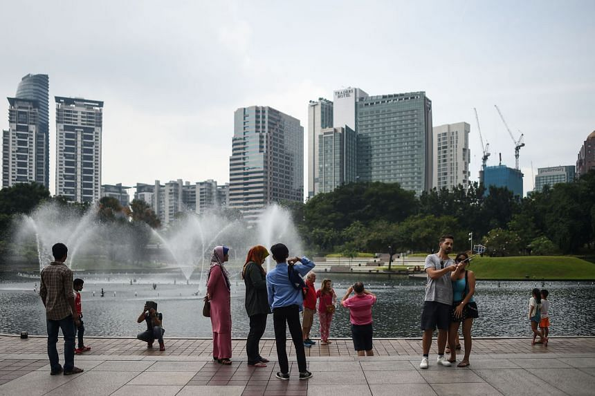 Tourists in a park in Kuala Lumpur. Trade-dependent Malaysia posted annual growth of 4 per cent in the second quarter, and avoiding a further decline could depend on domestic demand staying resilient.