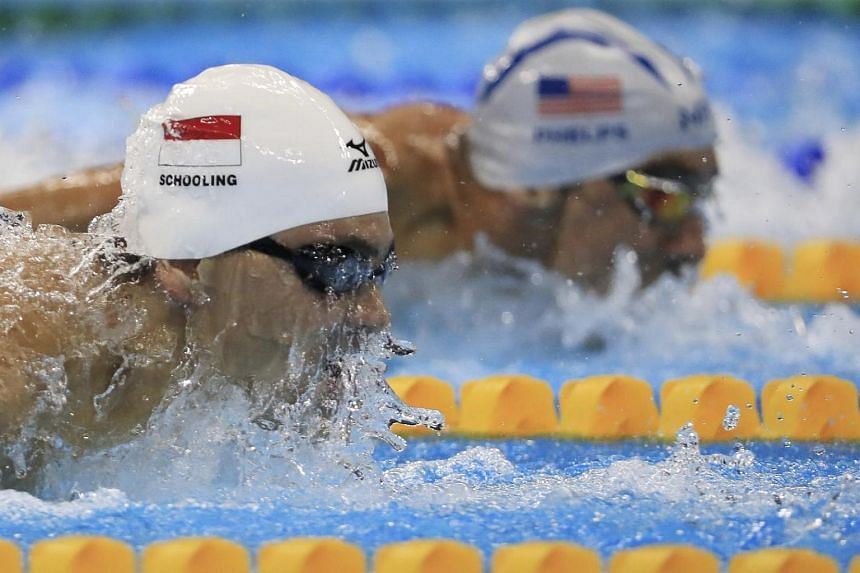 Joseph Schooling (front) competes with Michael Phelps during the Men's 100m Butterfly heats.