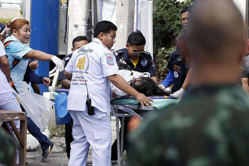 Thai rescue workers rush an injured bomb victim to a hospital following a bomb attack at the city clock tower in the center of Hua Hin, Thailand, on Aug 12.