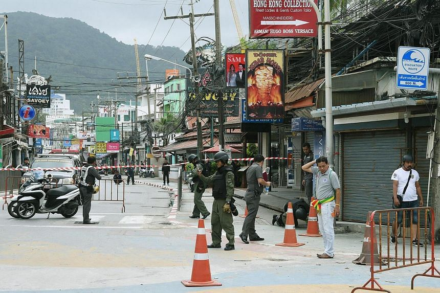 Thai members of the Explosive Ordnance Disposal (EOD) and other officials inspect the scene where a bomb exploded at a Police box station in the Patong beach area, in Phuket province, southern Thailand, on Aug 12. PHOTO: EPA