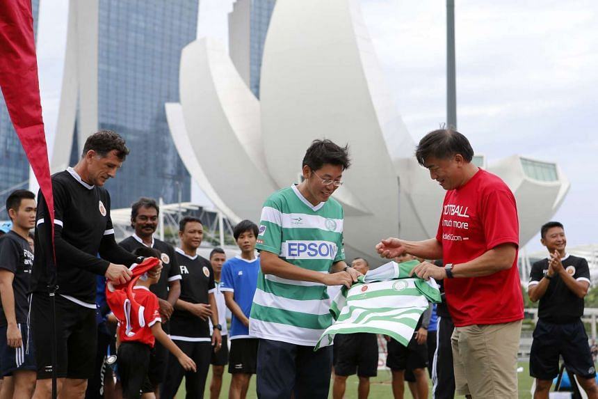 Sport Singapore CEO Lim Teck Yin (in red), and Geylang International Football Club Chairman Ben Teng (in green) exchange jerseys while Mr Aleksandar Durik (extreme left), Principal of Active SG Football Academy, looks on.