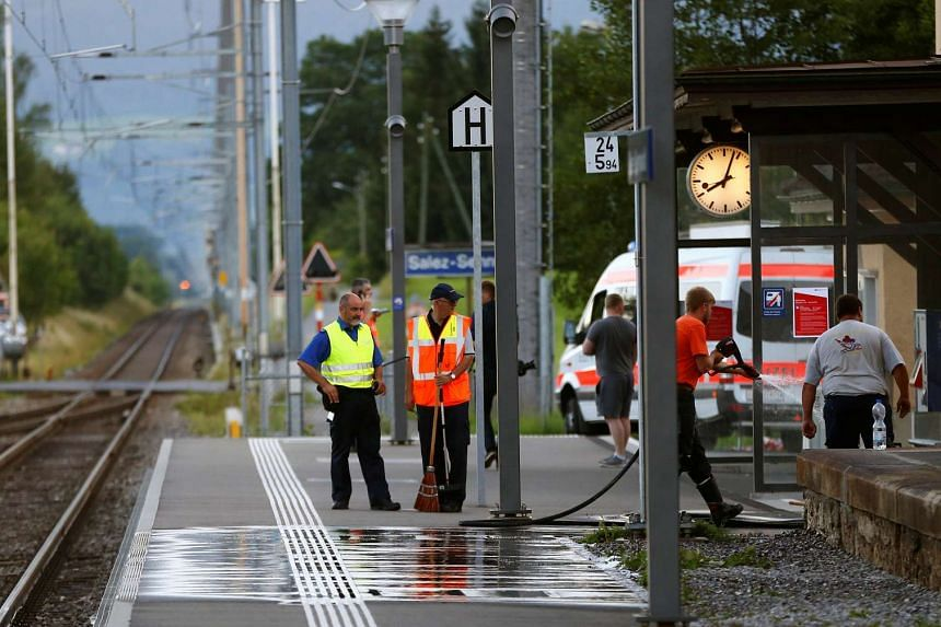 A Swiss police officer stands near workers cleaning a platform after a 27-year-old Swiss man's attack on a Swiss train at the railway station in Salez on Aug 13, 2016.