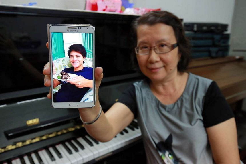 Music teacher Yim Kam Ling holding up pictures of her nephew Joseph Schooling, who won Singapore's first ever gold medal at the Rio Olympic Games on Saturday (Aug 13).
