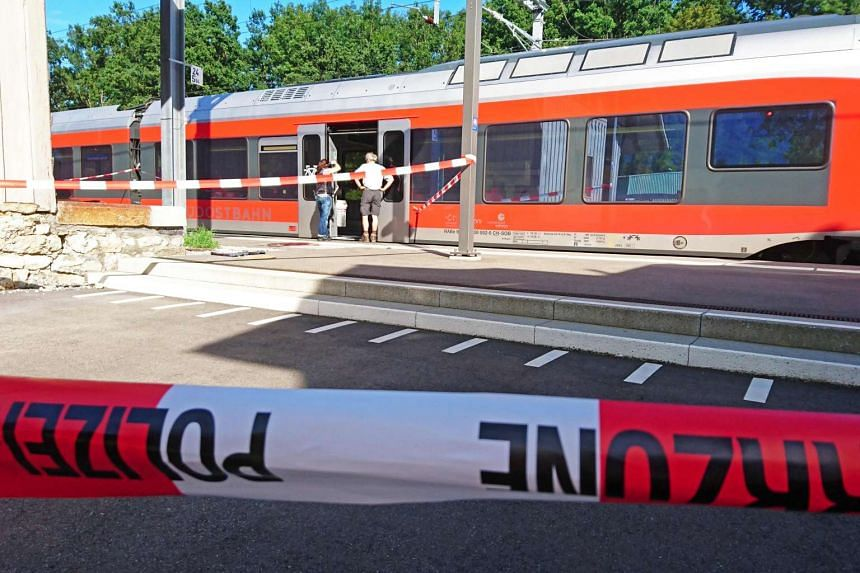 Policemen stand by a train at the station in Salez, eastern Switzerland, after a man set a fire and stabbed passengers on Aug 13, 2016.