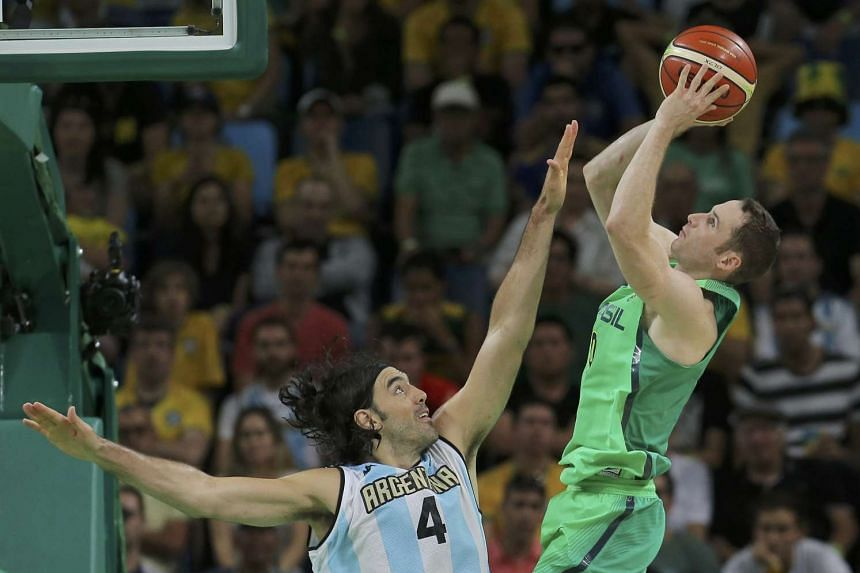 Marcelinho Huertas of Brazil shoots over Luis Scola of Argentina during the Men's Preliminary Round Group B match between Brazil and Argentina.
