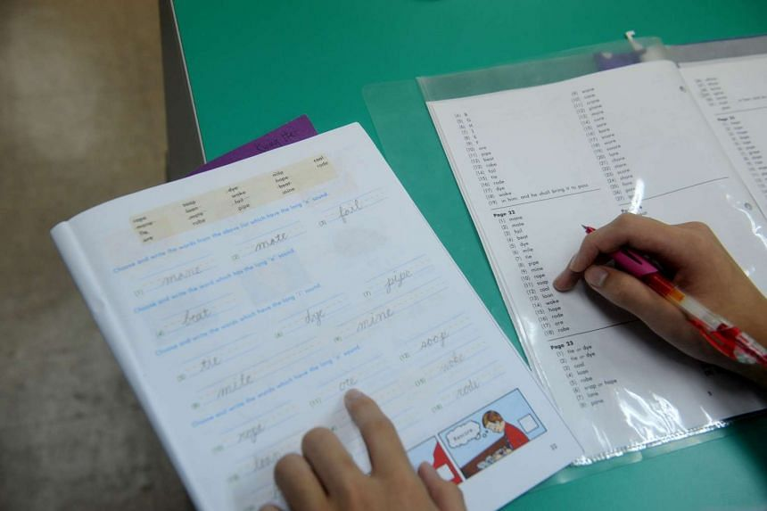 Students at Victory Life Christian School checking their answers from their Packet of Accelerated Christian Education booklets (left) with the provided answer keys at a scoring station placed in the middle of their classrooms.