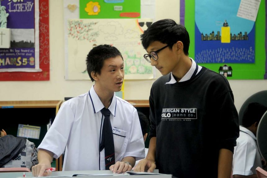 Junior High student Yim Kwing Hei (left) gets help from a classmate, Kim Young In at the scoring station. He has only been enrolled into the school for a week after receiving an approval from the Ministry of Education.