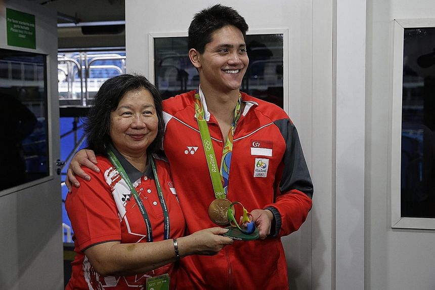 Above: Joseph Schooling with his mother May after winning the men's 100m butterfly final in Brazil yesterday. Right: His father, Colin (seated second from right), celebrating with family and friends during the live telecast of the race.