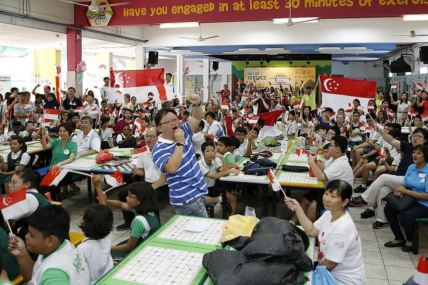 """Juying Primary School pupils cheering along with teachers and parents, while waiting for the live telecast of Schooling's race yesterday. Parliamentary Secretary for Ministry of Education Low Yen Ling (in green T-shirt) was also present. """"Do you want"""