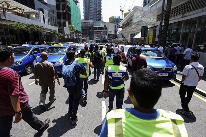 Taxi drivers blocking the roads in Kuala Lumpur in March in a protest against Grab's RM1 (33 Singapore cents) ride promotion. Taxi-driver associations have repeatedly warned the government against legalising their competitors which use ride-hailing a