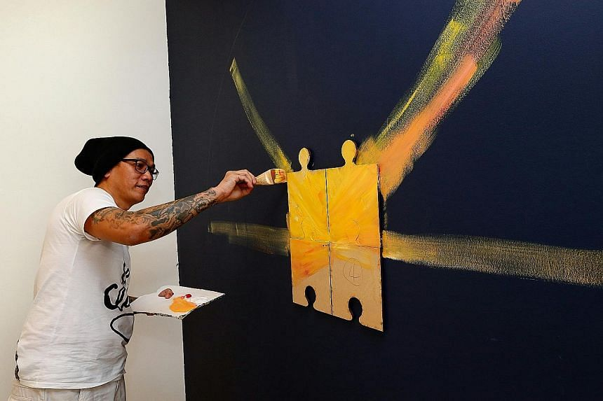Mr Yeow, who has spent half his life going in and out of jail, working on his wall art for the Yellow Ribbon exhibition at the Singapore Art Museum. It is his first contribution to the show done outside the prison walls - he was released in April las