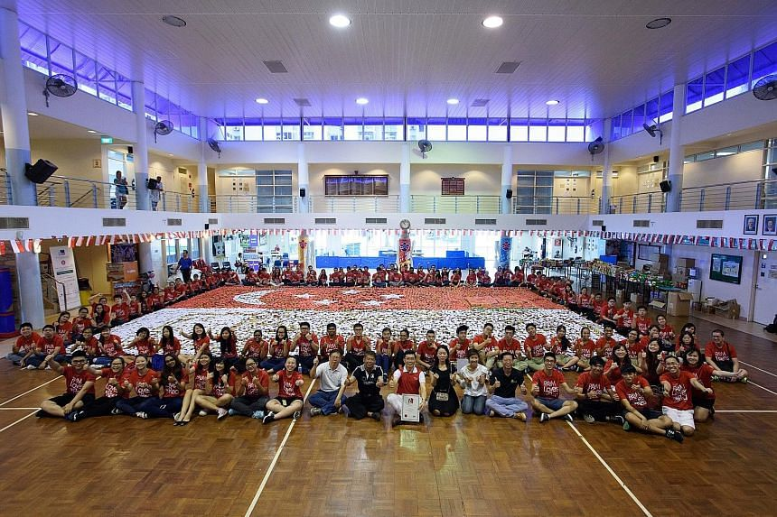 Volunteers with the Singapore flag that was made using 16,517 donated cans of food. The flag, measuring 12.8m by 8.9m, made it into the Singapore Book of Records.
