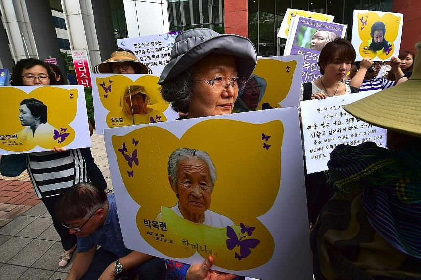 South Korean activists holding portraits of former comfort women during a rally in Seoul last month against the Reconciliation and Healing Foundation, which was set up to support comfort women. The landmark deal between South Korea and Japan to settl