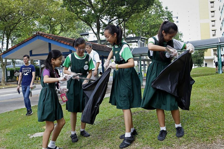 Juying Primary School pupils (from left) Chong Jin Yi, 11, Lily Zhang, 12, Wang Xin Yue, 12, and Chrystal Lee, 11, picking up rubbish at the HDB block opposite their school in Jurong West. Yesterday, Juying became the first school to take part in a p