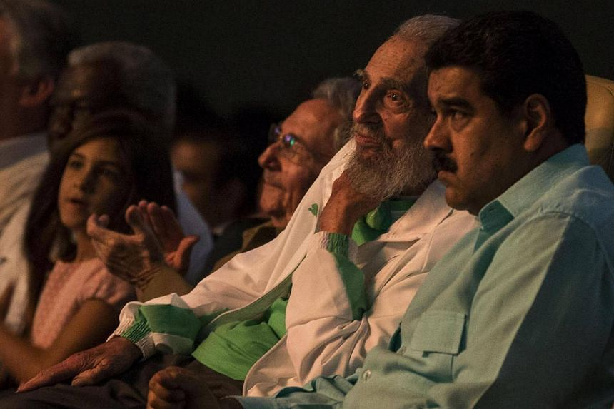 Former Cuban President Fidel Castro (centre), sitting next to Venezuelan President Nicolas Maduro (right), is seen attending the celebration of his 90th birthday at Karl Marx theatre in Havana on August 13.