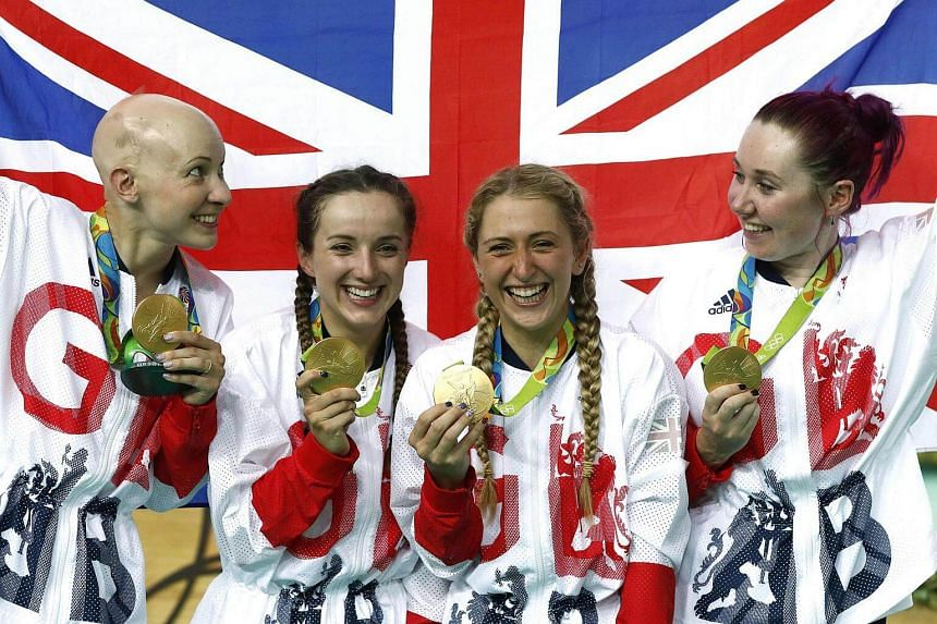 (From left) Britain's Joanna Rowsell-Shand, Elinor Barker, Laura Trott and Katie Archibald pose with their national flag and gold medals, after the women's Team Pursuit finals track cycling event.
