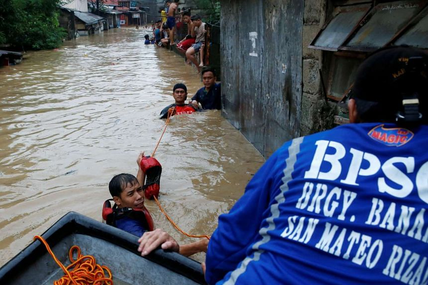 Rescuers evacuating residents after their homes were swamped by floods caused by monsoon rains in San Mateo, Rizal, the Philippines, on Aug 13, 2016.