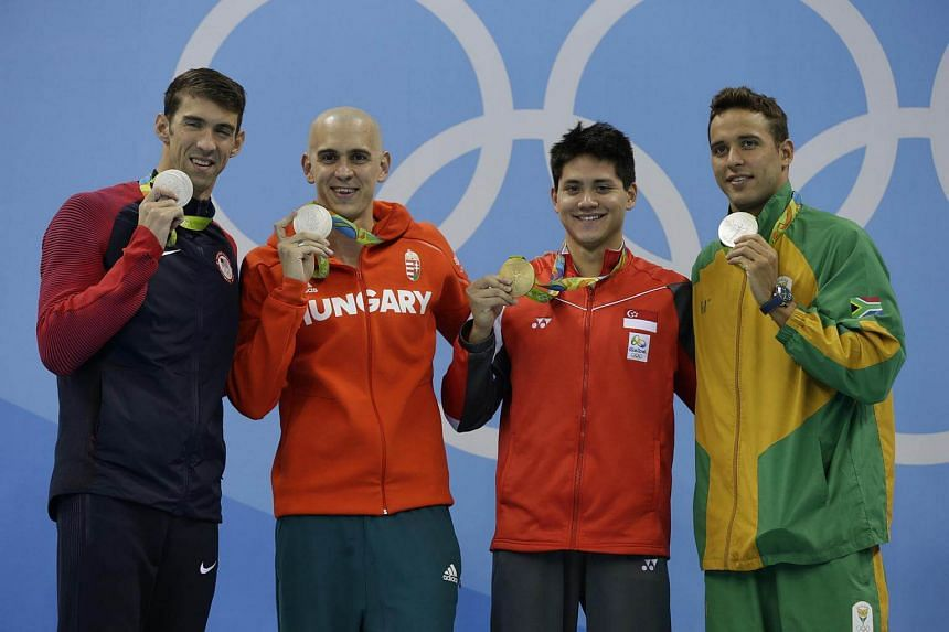 Joint silver medalists Michael Phelps (left), Chad le Clos (right) and Laszlo Cseh (second, left) with Joseph Schooling on the podium after he won the Rio 2016 Olympic Games men's 100m butterfly final on August 12.