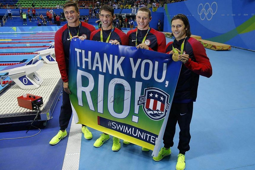 "US gold medalist team (from left) Nathan Adrian, Michael Phelps, Ryan Murphy, Cody Miller, pose with a banner ""Thank You Rio"" during the podium ceremony of the Men's swimming 4 x 100m Medley Relay Final, on August 13."