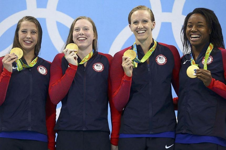 USA's Kathleen Baker, Lilly King,  Dana Vollmer and Simone Manuel pose with their gold medals.