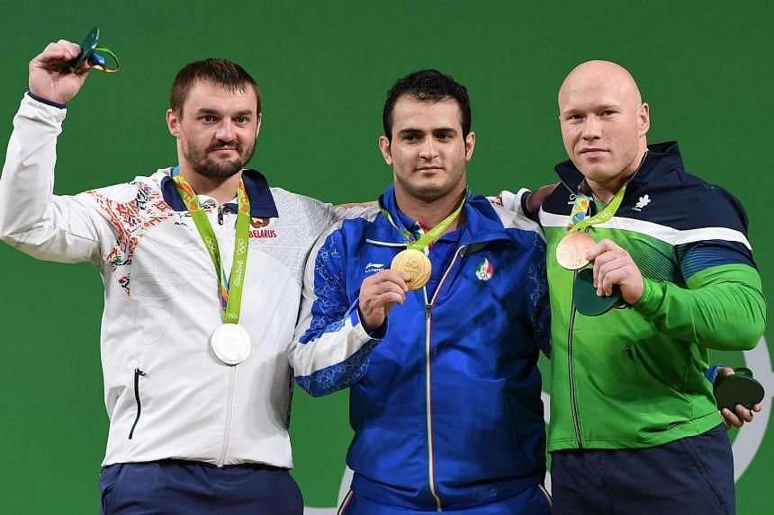 Iran's Sohrab Moradi (centre), gold, Belarus' Vadzim Straltsou, silver, and Lithuania's Aurimas Didzbalis, bronze, pose during the podium ceremony of the men's weightlifting 94kg event.