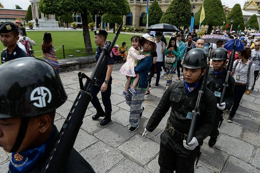 Tourists watch as Thai soldiers in vintage uniforms patrol the Grand Palace in Bangkok on August 14.
