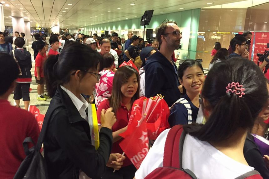 Flags being handed out to welcome Joseph Schooling home.
