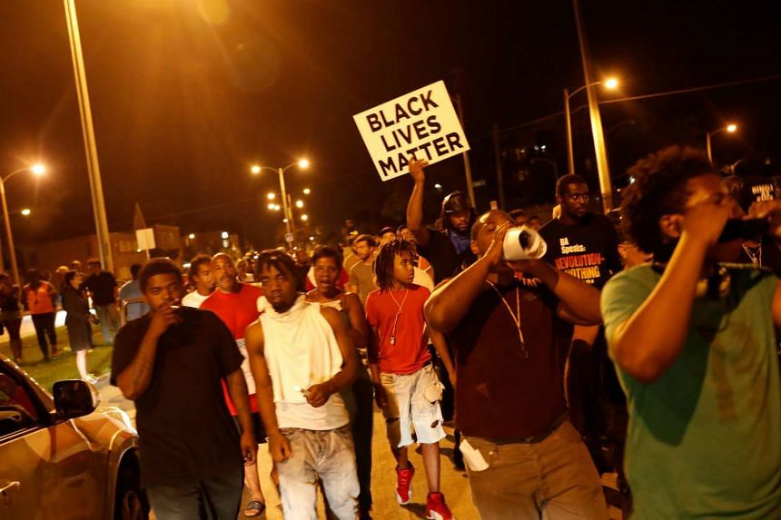 Protestors march during disturbances following the police shooting of a man in Milwaukee, Wisconsin on Aug 14, 2016.