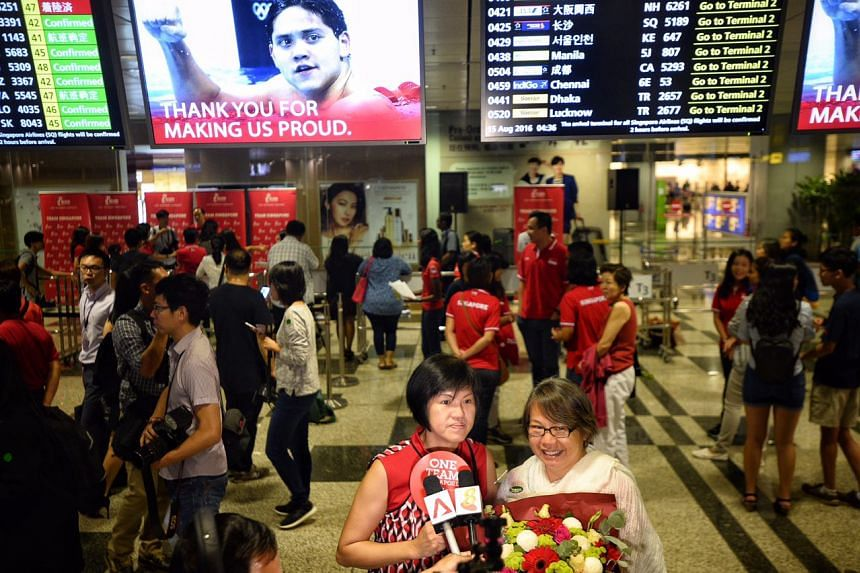 Supporters being interviewed with the flight times board featuring a congratulatory message.