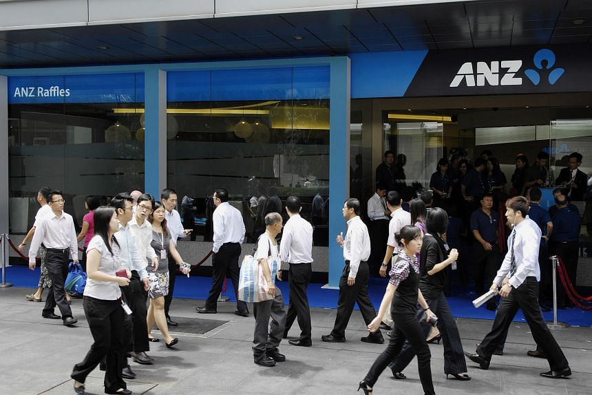 Pedestrians walk past an ANZ bank branch in the central business district in Singapore on May 16.