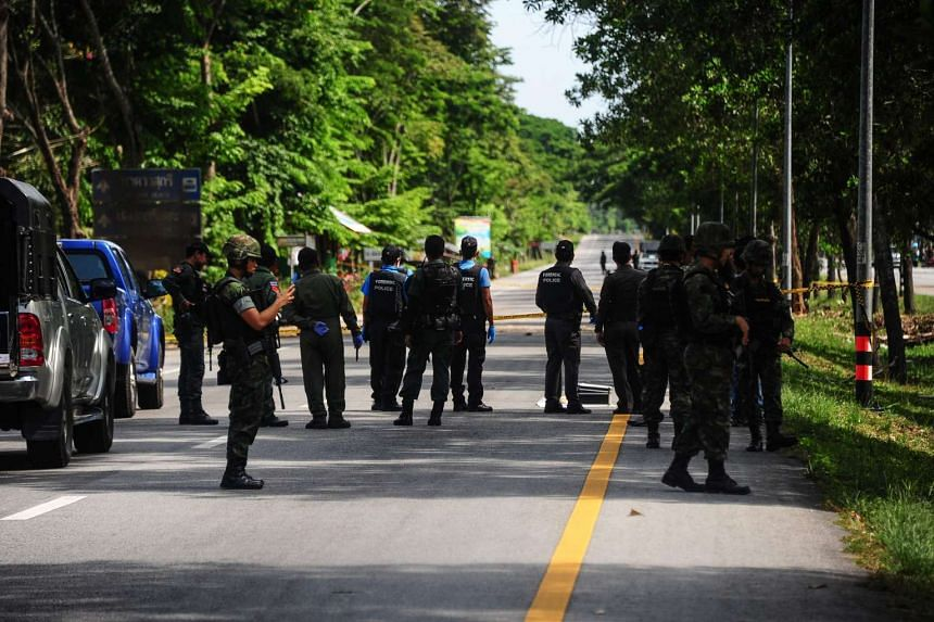 Thai soldiers watch as a forensic unit inspects the scene of an attack following two roadside bomb blasts at four separate locations in the Bacho district of Thailand's restive southern province of Narathiwat on August 15.