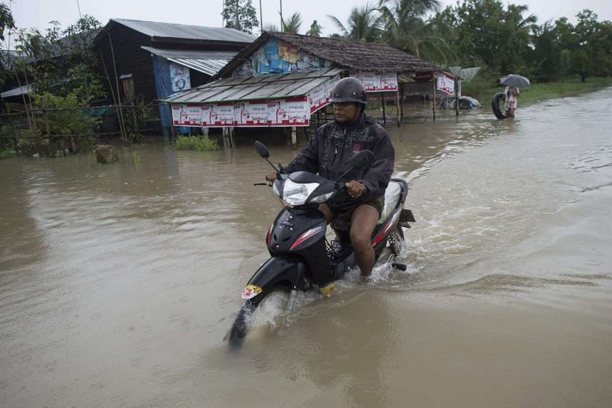A man riding a motorcycle through a flooded street in Pathein after seasonal rains in the Irrawaddy region, Myanmar , on Aug 12, 2016.