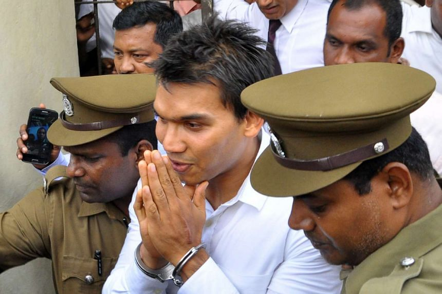 Sri Lankan member of parliament Namal Rajapakse (centre) is taken in handcuffs after he was remanded in custody for a week in Colombo on July 11, 2016.